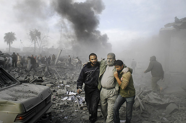 An injured Palestinian is helped from the rubble after an Israeli missile strike in Rafah, Gaza Strip.