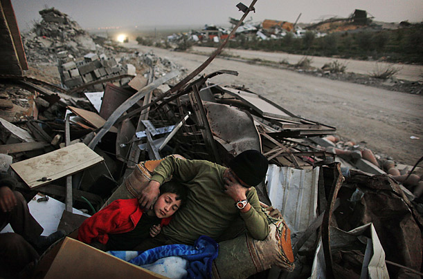 A family rests in the rubble of their home in Gaza.