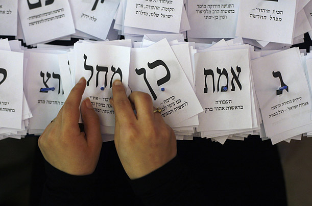 An election official holds a ballot for the Likud party while tallying votes at the Knesset, Israel's parliament, in Jerusalem.