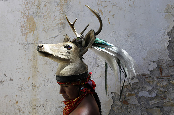 A dancer wearing a deer head poses for a photo during an Aztec ceremony to celebrate the birth of Cuauhtemoc, the last Aztec emperor, in Ixcateopan, Mexico.