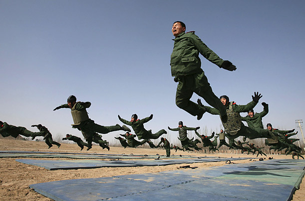 Police fly through the air during a training session at a military base in Yinchuan, China.