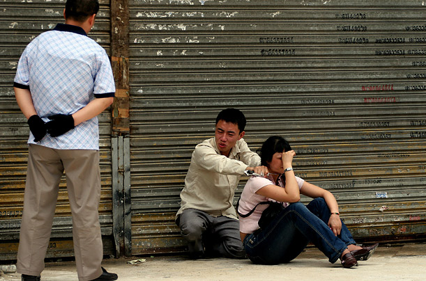 A Chinese policeman tries to convince a knife-wielding man to release a hostage on a street in Guangzhou, China. The man and his brother kidnapped the passer-by in a desperate bid to raise money for their mother's medical treatment.