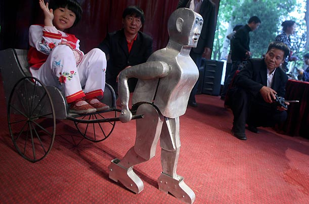 Wu Yulu (R), a Chinese farmer, builds robots of his own designs, using nothing but scrap and a fifth-grade education.