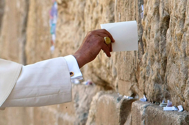 Pope Benedict XVI places a written prayer in the cracks of Jerusalem's Western Wall.
