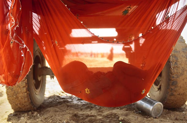 A hammock tied under a water tanker gives shade and rest to a young child whose parents work at a road construction site in Gurgaon, India.