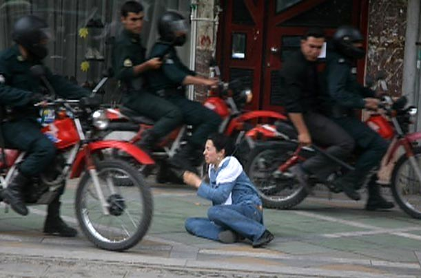 Iranian security personnel, among the thousands deployed to keep the peace after a week of election-related protests, ride past a woman sitting on the ground in Tehran.