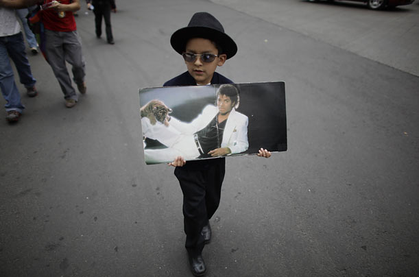 A Michael Jackson admirer holds a picture of the pop star during a vigil in Mexico City.
