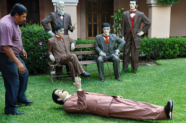 A statue of ousted Honduran President Manuel Zelaya lies on the grass in front of Honduran national heroes in Tegucigalpa.