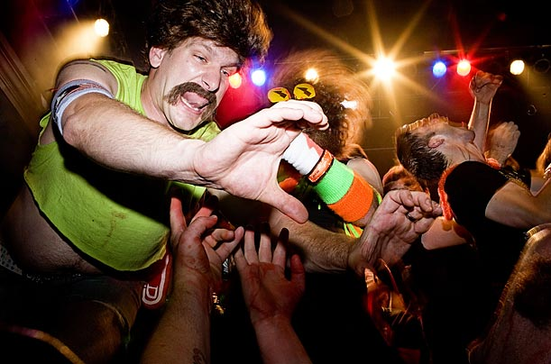 A performer reaches out to the audience during a free-for-all collaborative air guitar rendition of the song
