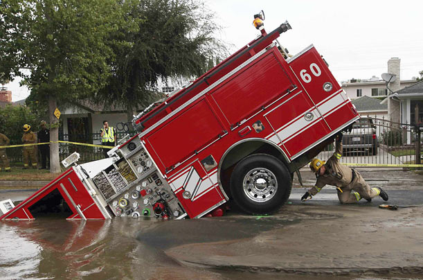 A fireman investigates a fire truck stuck in a sinkhole in the Valley Village neighborhood of Los Angeles.