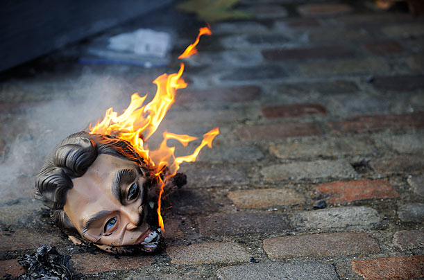 A mask representing former British Prime Minister Tony Blair burns in effigy outside the Queen Elizabeth II Conference Centre in London, on the fifth day of the Iraq war inquiry.
