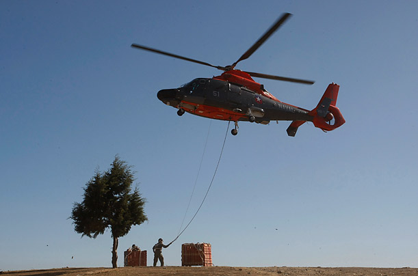 A helicopter unloads aid for earthquake victims in Constitucion, Chile, Tuesday, March 9, 2010.  An 8.8-magnitude earthquake hit central Chile last Feb. 27,
