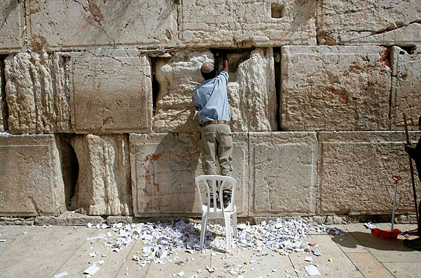 A man removes worshiper's notes from the crevices of the Western Wall in Jerusalem.