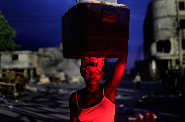In Port-au-Prince, a car's break lights illuminate a woman as she balances a cooler of drinks for sale in her head.
