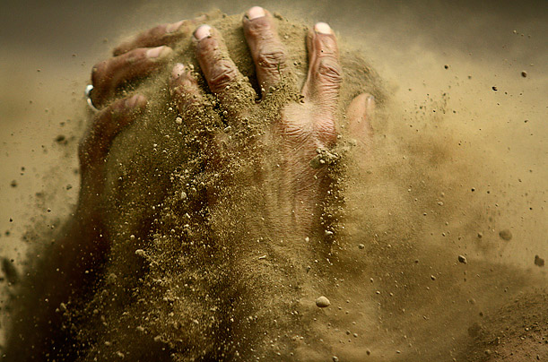 A traditional Indian wrestler smears mud on himself during a practice session in Calcutta, India.