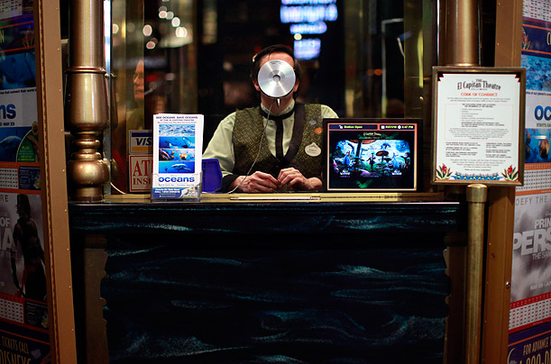 A sales attendant sits in the box office at the El Capitan Theatre in Los Angeles, California.