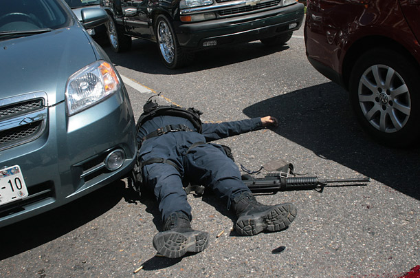 A Mexican Federal Police officer lies dead after a drug related shoot-out in Acapulco, Mexico.