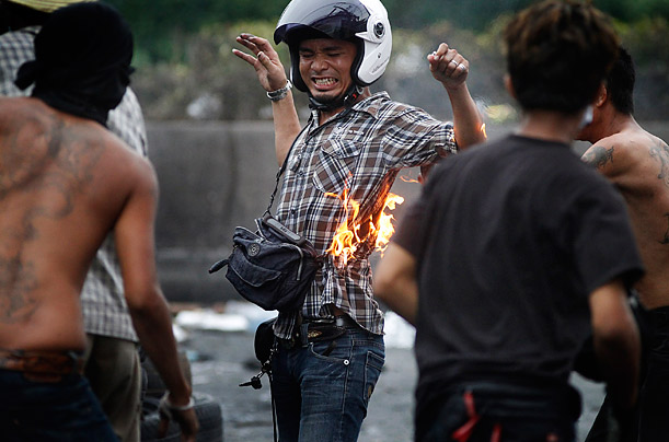 An anti-government protester accidentally lights himself on fire while throwing a molotov cocktail during a demonstration in Bangkok, Thailand.