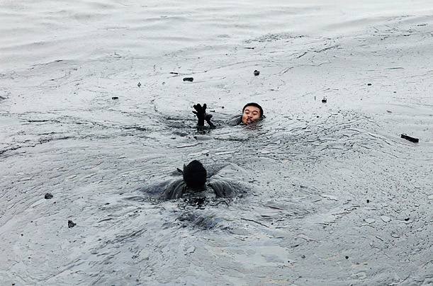 A worker attempts to rescue his co-worker, who was trying to fix an underwater pipe, from drowning in an oil slick created by an explosion at an oil storage facility in Dalian, China.