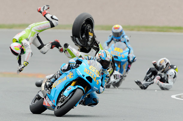Ducati rider Aleix Espargaro of Spain, left, loses control as he passes by crashed Honda rider Randy de Puniet of France, far right, during the Grand Prix of Germany in Hohenstein-Ernstthal, Germany.