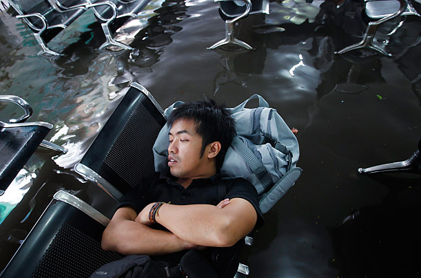 A man sleeps while waiting for his train in a flooded station in