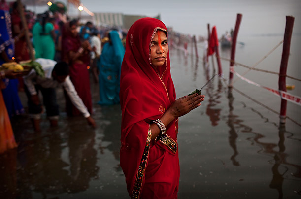 An Indian woman from the state of Bihar holds incense as she offers prayers in the Yamuna River on the Hindu holiday of Chaath Puja in New Delhi. On Chhath, an ancient Hindu festival, rituals