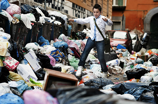 A child walks through piles of garbaged in the streets of Naples, Italy.