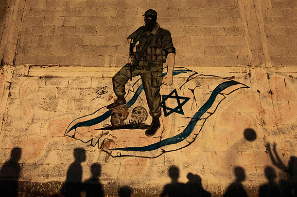 Palestinian children's shadows are cast against a wall while playing in front of an anti-Israel mural in Gaza City.