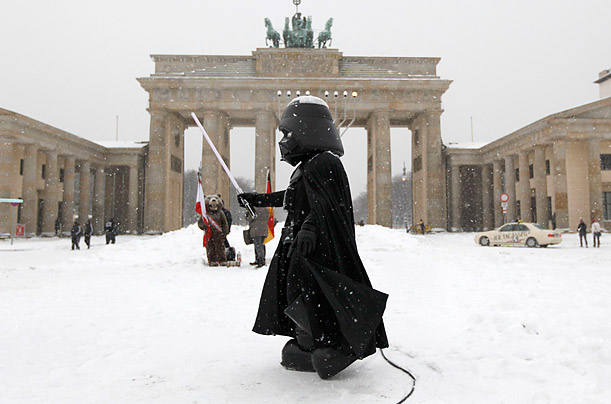 A street performer dressed as Darth Vader from the film 'Star Wars' stages in front of the Brandenburg Gate in Berlin, Germany.