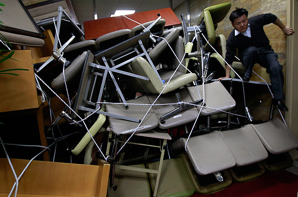 An opposition party member climbs over an obstacle constructed of furniture by members of his group.
