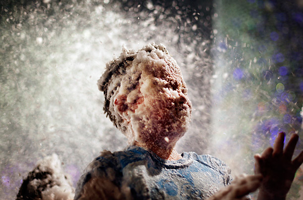 A child's face is covered with foam used to simulate snow at a shopping mall in Singapore.