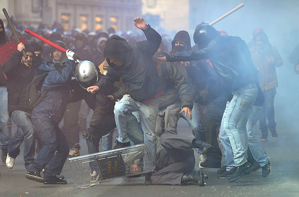 A policeman is beaten by demonstrators protesting to demand changes within government in Rome.