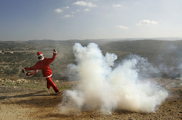 A Palestinian protester in a Santa Claus costume runs away from a tear gas canister fired by Israeli troops during a protest outside the West Bank village of Bilin.