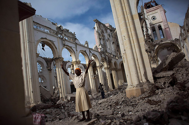 A woman prays among the remains of the main cathedral in downtown Port-au-Prince, Haiti.
