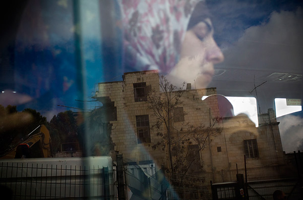 The Shepherd Hotel is reflected on a window of a passing bus in east Jerusalem.  Bulldozers demolished the historic hotel to make way for a new Israeli enclave.
