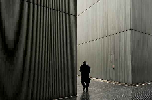 An office worker walks through a narrow alleyway between two office buildings in central London.