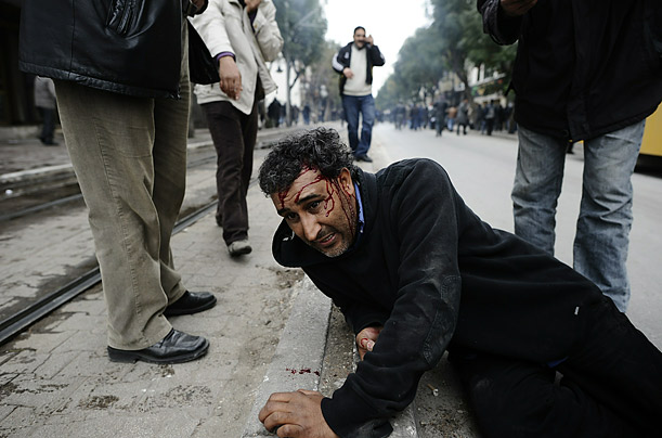 A man lies injured during a clash with riot police in Tunis. Protesters were tear-gassed while demonstrating against Tunisia's new government.