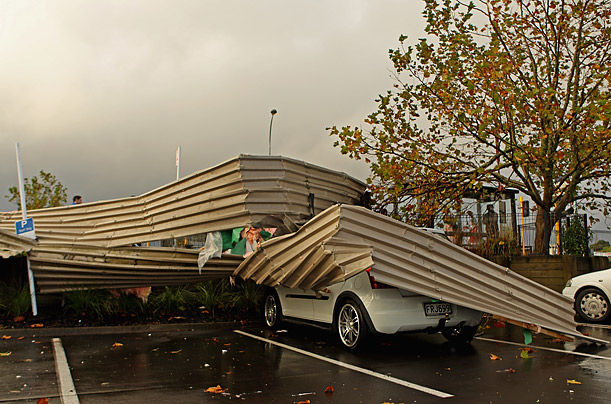 Debris wraps around a car at the Albany MegaCentre after a tornado struck the area in Auckland, New Zealand.